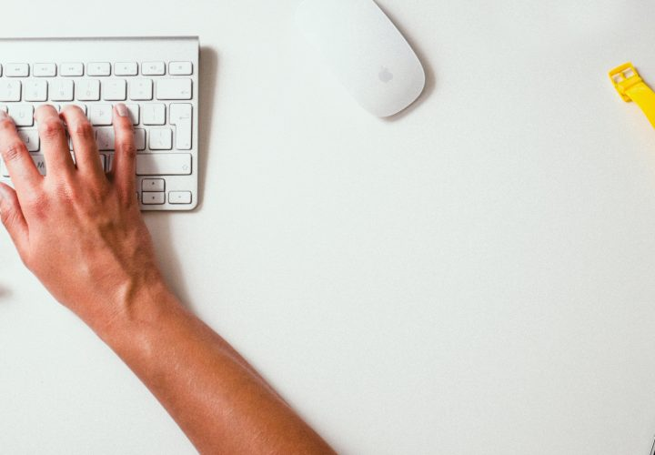 Hands typing on apple keyboard
