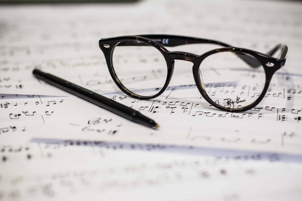 pen and glasses sitting on a music score