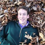 American Jazz Composer Ben Morris smiling on a pile of fall leaves