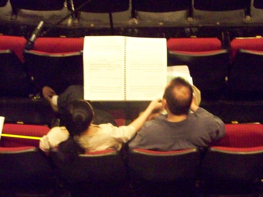 Arial view of two American composers reading a large orchestral score