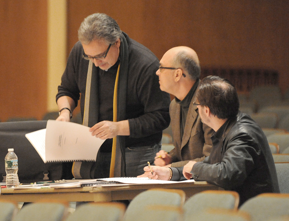 three composers reviewing a score